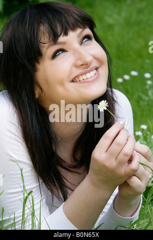 Smiling woman holding daisy lying in grass - Stock Photo