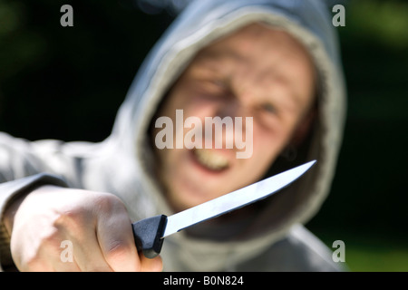 young man holding a knife - Stock Photo