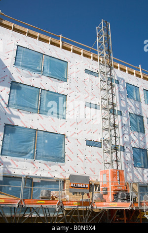 Construction site lift and block of flats wall covered with Paroc Tyvek stone wool insulation panels. - Stock Photo