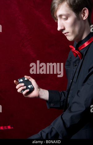 young magician doing a card trick - Stock Photo