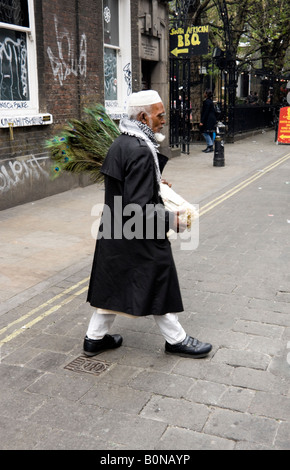 elderly Bangladeshi man crossing Brick Lane with peacock feathers to sell - Stock Photo