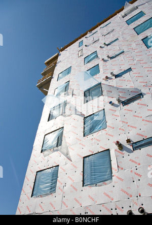 Construction site , wall of block of flats covered with Paroc Tyvek stone wool insulation panels. - Stock Photo