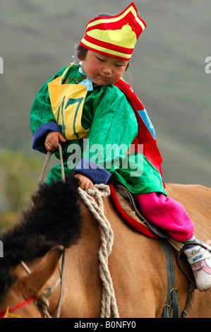 Four year old girl riding a horse participant in the horsemanship competition of the Naadam Festival, Mongolia - Stock Photo