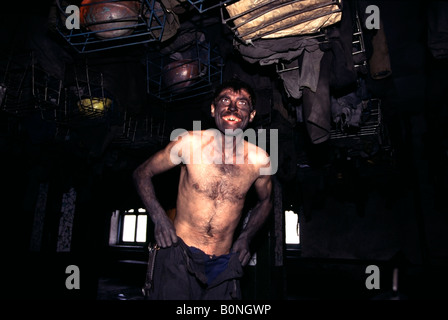 Coal Miner Blackened by coal dust in the changing room after working all night over in a Russian coal mine - Stock Photo