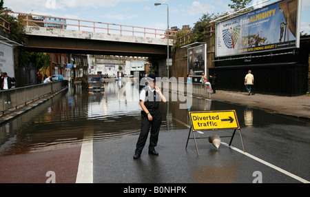 Female police officer standing near a diverted traffic sign board on the road, London, England - Stock Photo