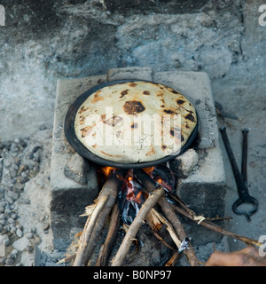 Roasted thick millet bread, Rotla, on hot earthen pan placed on hand built wood burning clay stove, ready to be - Stock Photo