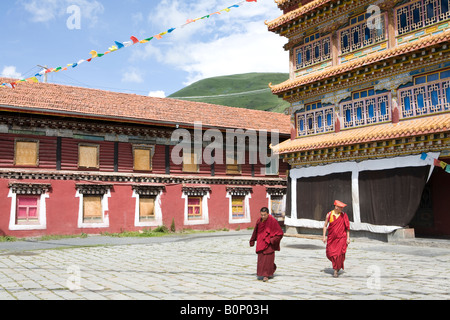 Two Tibetan Buddhist priest walking in front of a lamasery - Stock Photo