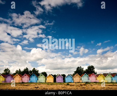 A row of colourful Beach Huts on West Mersea beach in Essex. - Stock Photo