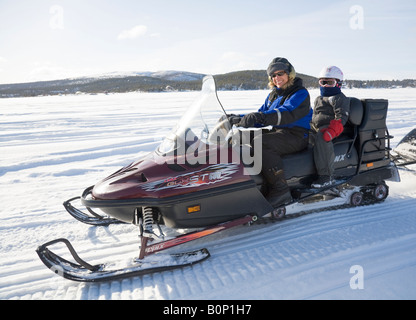 A woman in her fourties rides a Lynx snowmobile in snowy Lapland, a six years old girl is sitting on the back seat - Stock Photo