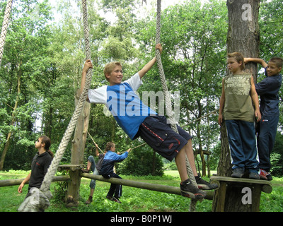 boy student holding on to climbing ropes at school camp - Stock Photo