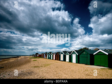 Heavy cloud over traditional Beach Huts on West Mersea beach in Essex - Stock Photo