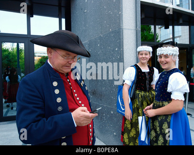 Man in historic costume using cellphone mobile phone with two girls laughing EU parliament Brussels Belgium - Stock Photo