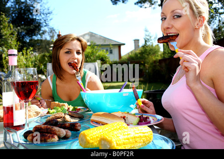 Young Women Eating Sausages Model Released - Stock Photo