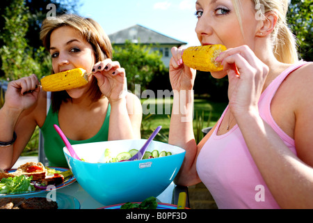 Young Women Eating Corn on the Cob Model Released - Stock Photo