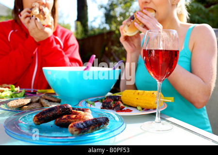 Young Women Eating Hotdogs Model Released - Stock Photo