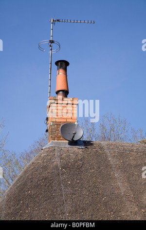 Satellite dish on a thatched roof alongside a chimney mounted TV ariel antenna. - Stock Photo
