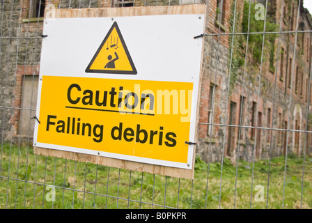 Sign on fence stating 'Caution Falling Debris' - Stock Photo