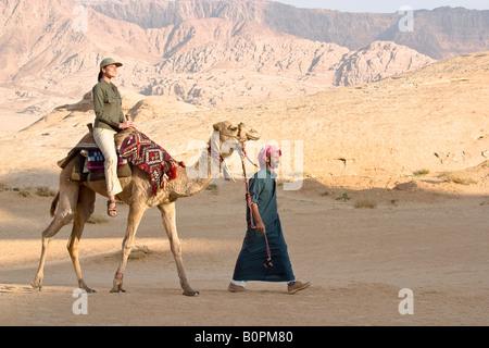 Jordan. Desert Wadi Ram. The young woman travels on a camel. - Stock Photo