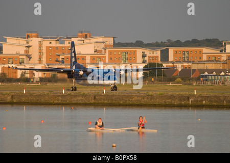 Airplane landing at London City Airport and two rowers training on the Royal Albert Dock - Stock Photo