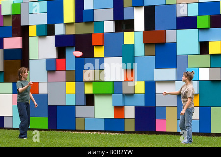 Women play frisbee at Discovery Green public park in Houston Texas - Stock Photo