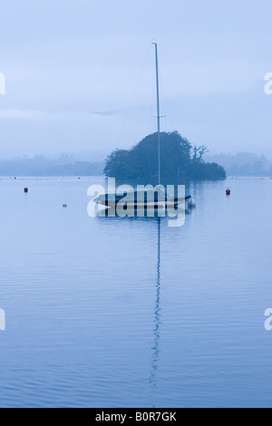 Moored yacht on a misty morning on Lake Windermere in the English Lake District, Cumbria, England, UK - Stock Photo