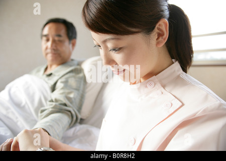 Nurse taking patient's blood pressure - Stock Photo