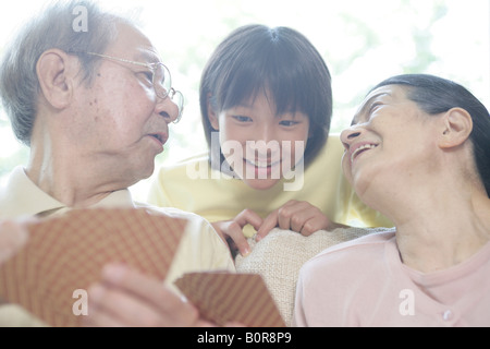 Boy (12-13) assisting grandparents playing cards, close-up - Stock Photo