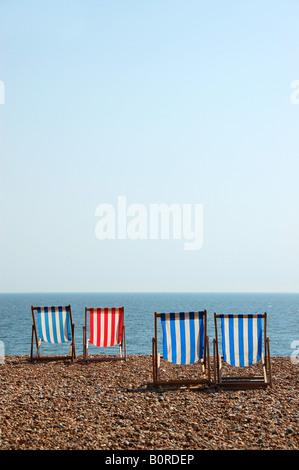 Deckchairs on Brighton beach, UK - Stock Photo