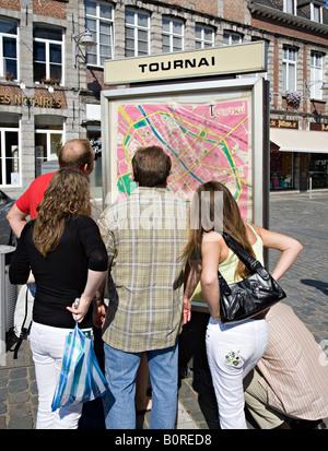 People gathered around town map Tournai Belgium - Stock Photo