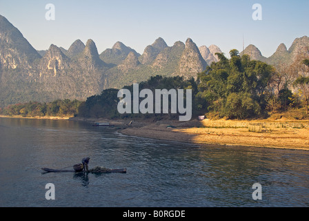 A Cormorant fisherman on a bamboo raft on the Li river between Guilin and Yangshuo in central China - Stock Photo