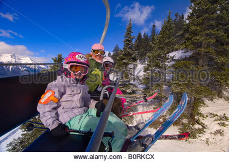 Children and their mother ride the chairlift at Lake Louise Mountain Resort Lake Louise Banff National Park Alberta - Stock Photo