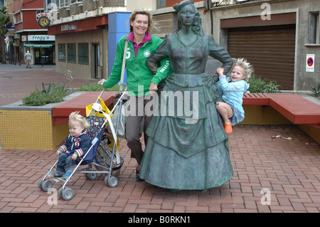 Gran Canaria Las Palmas a happy family posing at a statue on the boulevard - Stock Photo