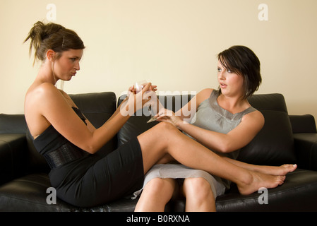 two women drinking on the sofa - Stock Photo