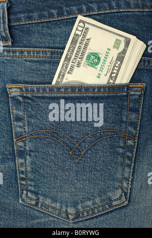 New dollar roll in hip pocket of worn blue jeans closeup - Stock Photo