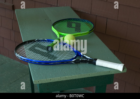 two colorful tennis rackets on bench yellow ball vacation cabin - Stock Photo