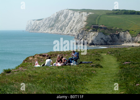 Picnic on cliff top four women having lunch overlooking the sea at Freshwater Isle of Wight England UK - Stock Photo