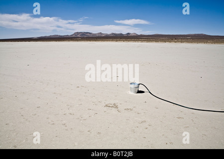 Bucket with a garden hose in the desert - Stock Photo