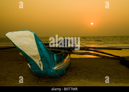 Outriger on beach in Sri Lanka at sunset - Stock Photo