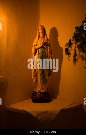 A small statue of the Virgin Mary on a shelf. - Stock Photo