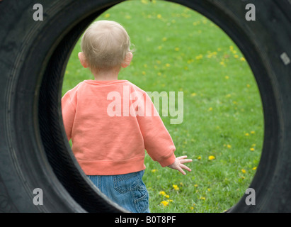 20 month old girl seen through a tire swing as she plays in the yard - Stock Photo