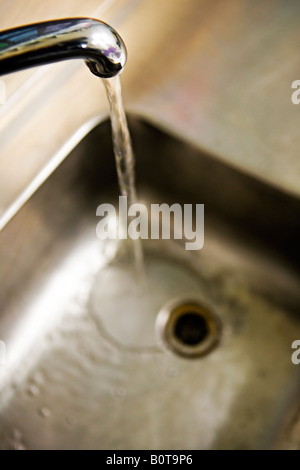 Water runs from tap into stainless steel sink - Stock Photo