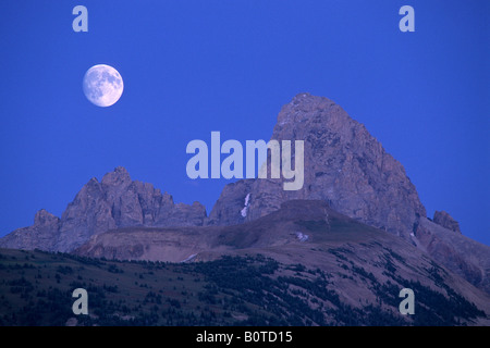 Moonrise over the Grand Teton from Targhee NF on the west slope of the Teton Range WYOMING - Stock Photo