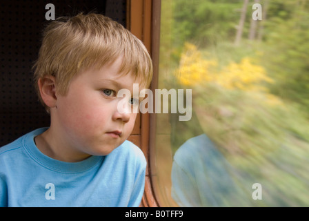Young Boy Looking Out Of Train Window - Stock Photo