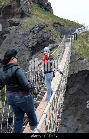two female tourists posing on the carrick a rede rope bridge on the county antrim coast northern ireland - Stock Photo