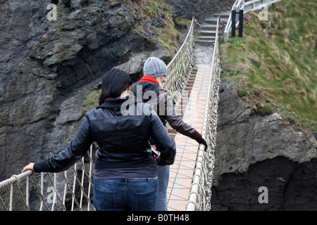 two female tourists walking across the carrick a rede rope bridge on the county antrim coast northern ireland - Stock Photo