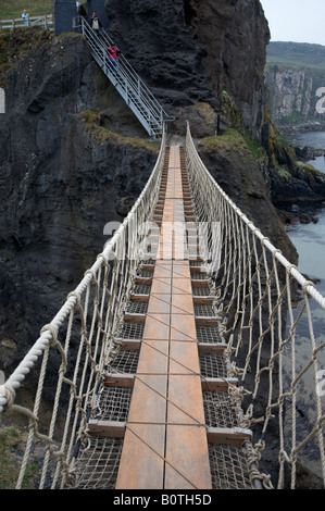 walking across the carrick a rede rope bridge on the county antrim coast northern ireland - Stock Photo