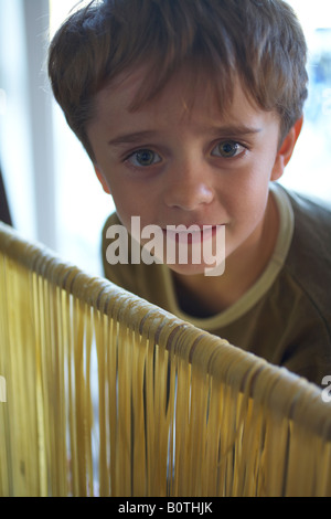 boy child looking over rail draped with freshly made pasta - Stock Photo