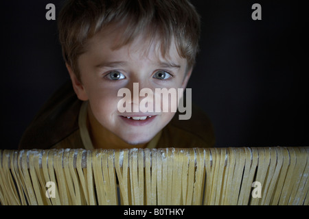 boy child looking over rail draped with pastafreshly made pasta - Stock Photo