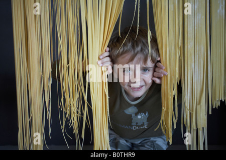 boy child looking through curtain of freshly made pasta - Stock Photo