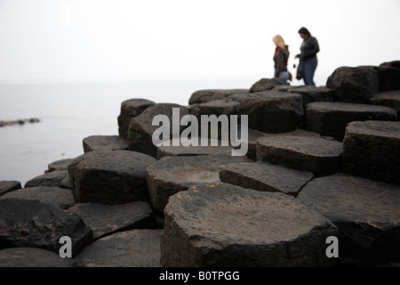two female tourists wander round the red basalt hexagonal rock formations at the giants causeway county antrim northern - Stock Photo